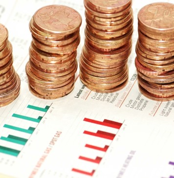 Business concept – Stacks of coins on various bar charts